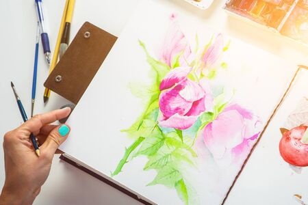 dogroses: Drawing album with painted peonies and dogroses on a white table, top view