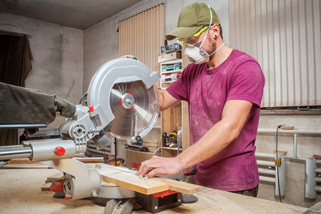 A man with work clothes and a cap carpenter cuts a wooden board on a large circular gray saw in a light workshop Banco de Imagens