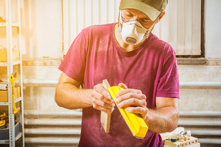 A man in a cap, safety mask, goggles and a T-shirt is sanding a wooden  in the workshop, side view, in the background a lot of tools