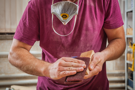 blacksmith: Close-up of a man with work clothes and protective gloves sanding a wooden block in a light workshop Stock Photo