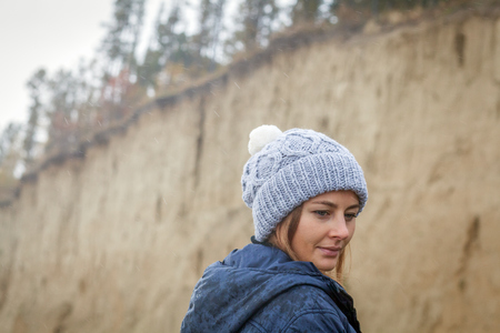Close-up A young dark-haired woman in a knitted gray cap made of natural wool, a blue jacket on a warm autumn day against the backdrop of a sand pit and coniferous forest
