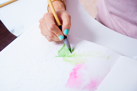 paintings: Close-up of a female artist paints a thin wooden brush and watercolor drawing of a pink peony flower in an album for drawing on a white background Stock Photo