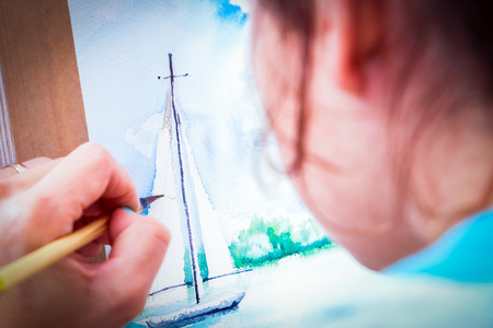 paintings: Close-up woman artist paints a thin wooden brush and watercolor drawing a yacht in the sea in an album for drawing Stock Photo
