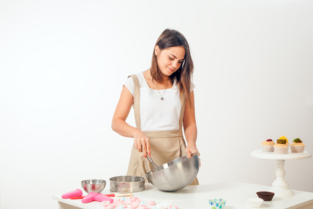 A young dark-haired female confectioner in a white T-shirt and in a beige apron    in a metal bowl, on the table stand a capcake on a white background