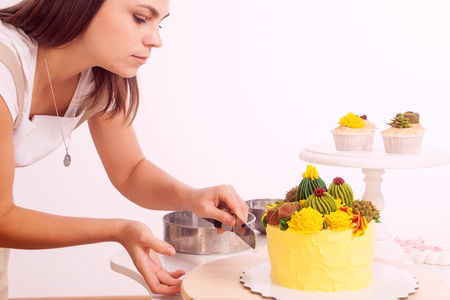 a young beautiful woman confectioner cuts a yellow colored homemade cake with bicqwits, a stuffing of currant and cheese, garnished with green ornaments and cacti, in the background of a crockery