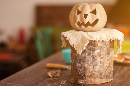 A small clay pumpkin with jacks face for halloween stands on a wooden stand on a wooden table in a beautiful workshop