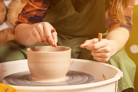 A potter in a plaid shirt and green apron beautifully sculpts a deep bowl of brown clay and cuts off excess clay on a potter's wheel in a beautiful workshop