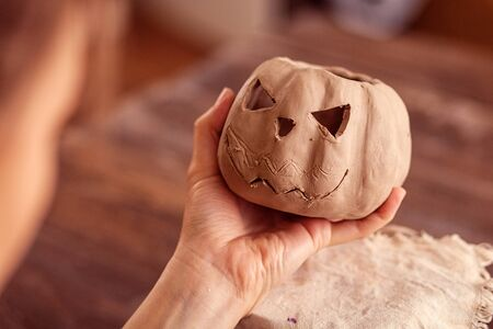 A close-up of a female potter holding in his hand a small pumpkin made of clay with a jacks face against the background of a wooden table