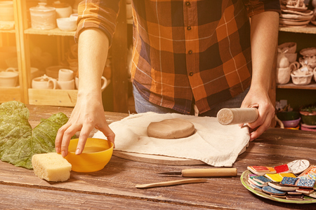 Woman  potter in a plaid shirt and jeans rolls out clay to make a plate on a wooden table in the workshop, on the table there are clay fakes, in the background, the shelves are in clay cups and vases Banco de Imagens