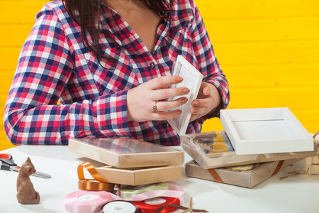 A confectioner in a checkered shirt packs boxes with chocolate sets, the packer forms chocolate gifts Foto de archivo