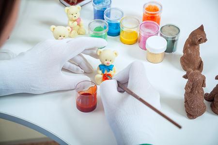Close-up d'un confiseur avec des gants médicaux peint un pinceau en bois avec une peinture rouge d'un ours polaire en chocolat au lait, sur une table blanche se trouvent une peinture Banque d'images - 88149114