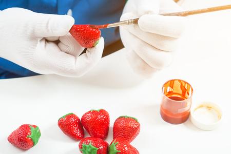 Close-up Une confiseuse en uniforme bleu et des gants médicaux peint un pinceau en bois avec de la peinture rouge une fraise de chocolat, sur une table blanche se trouvent d'autres fraises rouges et une peinture Banque d'images - 88149118