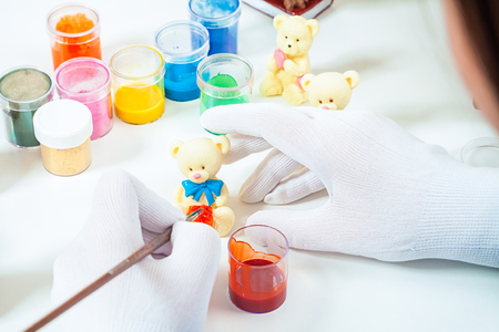 Close-up of a confectioner with medical gloves paints a wooden brush with a red paint of a polar bear made of milk chocolate, on a white table lie a paint