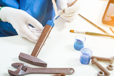 Close-up of a woman a confectioner in blue uniform and white gloves paints a hammer of milk chocolate with edible paint, not a white table, a wrench, brushes, paints Stock Photo