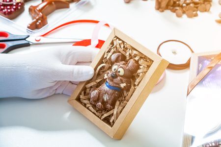 Close-up of a woman wearing a gloves confectioner is holding a box of candy in the form of a dog of their milk chocolate for the new year 2018.A gift for Christmas from sweets for children and adult