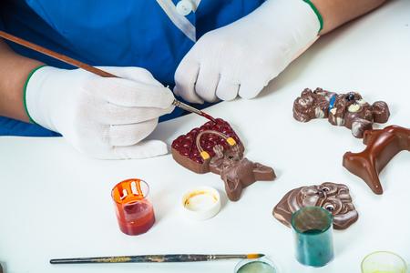 Primer plano de una mujer un pastelero en uniforme azul y guantes pinta un caramelo de chocolate en forma de un perro de la lechería Chocolate belga con pintura comestible, en la mesa se encuentran otros perros dulces de Navidad Foto de archivo - 88440620