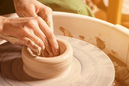 Close-up woman potter sculpts a deep plate of brown clay on a potters wheel in the workshop