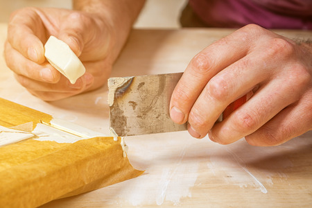 Close-up A male carpenter in work clothes restoring a vintage beige door with wax and a spatula on a wooden table
