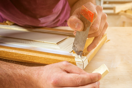 Close-up A male carpenter in work clothes restoring a vintage beige door with wax