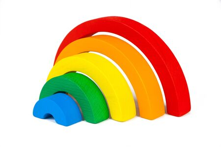 Wooden toy of seven different-colored arcs in the form of a rainbow on a white isolated background, arcs folded in the form of a ladder