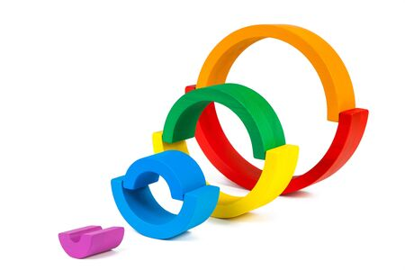 A wooden toy of seven different-colored arcs in the form of a rainbow on a white isolated background, the arcs are folded in the form of circles Stock Photo
