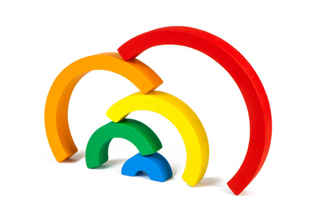 A wooden toy of seven different-colored arcs in the form of a rainbow on a white isolated background, the arcs are stacked on top of each other