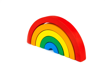 A wooden toy of seven different-colored arcs in the form of a rainbow on a white isolated background, the arcs are folded like a rainbow