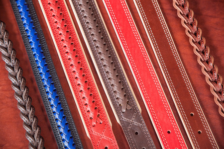 A close-up of narrow belts made of genuine red, blue and brown leather. Pattern made of leather belts Stock Photo