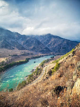 Autumn scenery of the Altai mountain Chemal region: high mountains, a mountain river Katun of turquoise color , a winding road, a forest, fields and a blue sky with clouds. View from high mountain.