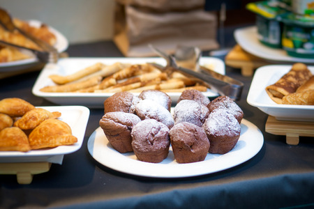 A variety of pastries for guests at a holiday on a dark table: chocolate cupcakes, decorated with sugar, pies made of puff pastry, pancakes, samsa.