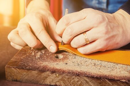 A close-up of a man skinner makes holes in the brown belt of full-length leather for fasteners on the wrinkled desk in the workshop. Saddler  manufactures a belt Stock Photo