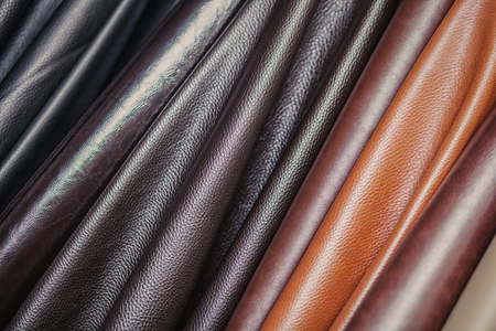 A close-up of multi-colored natural leather: black and different browns. Pattern made of genuine leather