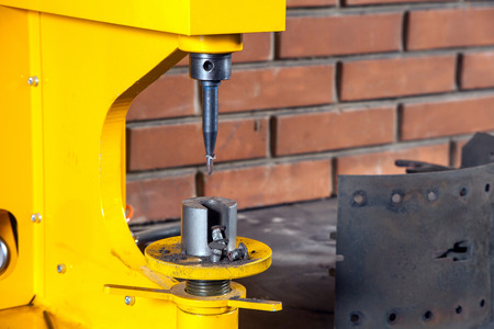 A close-up of yellow riveter machine for riveting brake pads  in the workshop in the background a brick wall