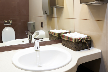 A close-up of a modern white sink, next to it there is a box with cleaned hand towels, automatic hand dryer, in the background a toilet in the toilet room for guests in a restaurant or hotel