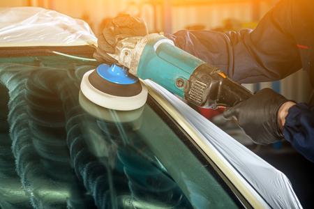 Close-up van een mannelijke monteur met een blauw prisma en beschermende handschoenen poetst het voorglas van de auto met een moderne groene polijstmachine tegen kleine krassen na de installatie Stockfoto