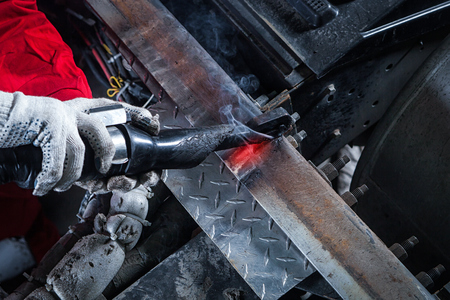 Close-up of a male mechanic in red uniform and protective gloves heats the metal by an induction machine in the workshop. Heating of the truck frame by means of an induction industrial heater, a soldering iron Zdjęcie Seryjne
