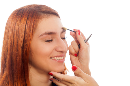 The master on the eyebrows holds in his hand tweezers and draws the shape of the grafted eyebrow shape  red-haired beautiful woman on a white background