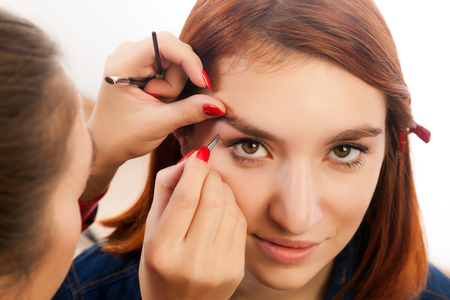 The master on the eyebrows draws the shape of the grafted eyebrow shape  red-haired beautiful woman on a white background