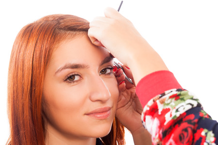 The master on the eyebrows corrects the eyebrow shape of the roach with tweezers   red-haired beautiful woman on a white background  Stock Photo