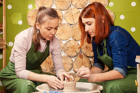 A woman potter teaches a red-haired woman to properly mold a bowl of brown clay on a potter's wheel in a bright workshop. Training of modeling on a potter's wheel