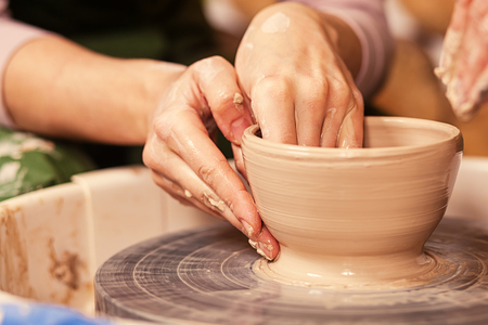 Close-up of a young woman potter sculpting on a potters wheel a vase made of brown clay, makes a smooth edge at the bowl in the creative workshop, side view Stock Photo