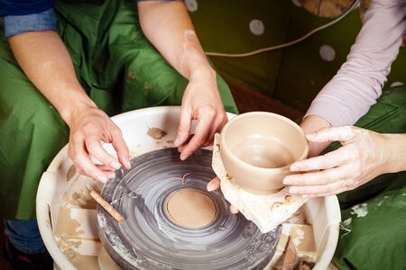 Close-up of a young woman potter teaches to sculpt a woman on a potters wheel a vase made of brown clay, cuts it off the potters wheel with a special thread, the top view
