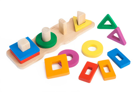 Photo of a wooden toy children's sorter with small wooden details in the form of geometric shapes in different colors on a white isolated background Foto de archivo