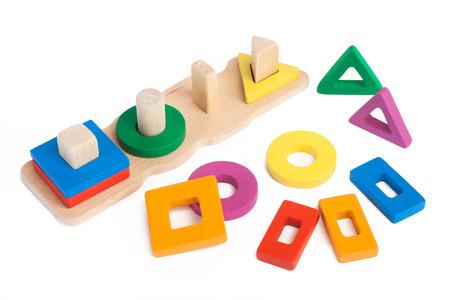 Foto di un selezionatore per bambini in legno giocattolo con piccoli dettagli in legno a forma di forme geometriche in diversi colori su uno sfondo bianco isolato Archivio Fotografico - 91669627