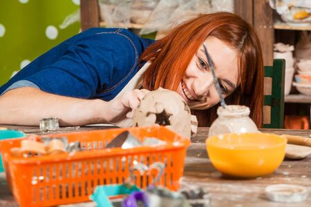 A young red-haired woman potter in an apron smiles and sculpts her hands with a clay candlestick in the workshop on a wooden table, in the background, racks with clay toys and tools Stock Photo