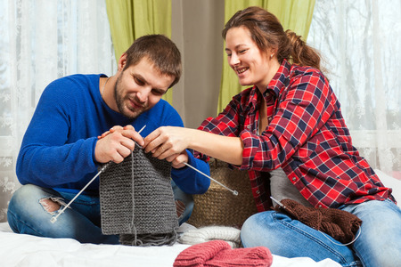 Young pregnant woman is teaching a young man in a blue sweater and jeans how to knit with knitting needles from a natural string of gray sweater, sitting on a bed in a home setting