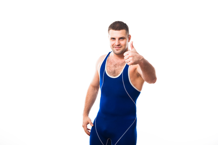 Young dark-haired man wrestling Greco-Rican wrestling, master of sports in grappling in blue wrestling tights smiling and holding his thumb up against white isolated background