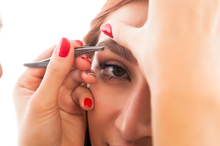 A womans eyebrow plucked her eyebrows red-haired woman to achieve the ideal shape in a beauty salon, side view. Eyebrow correction procedures Stock Photo