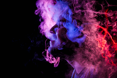 Man is admiting puffs of steam from the electronic cigarette, cloud of colored smoke of red and pink color on a black isolated. Harm to smoking on the example of a young mugger