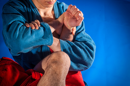Man wrestlers of grappling and jiu jitsu in a blue and red kimono makes submission wrestling. Fighting techniques:   armbar, armlock 免版税图像 - 92869236